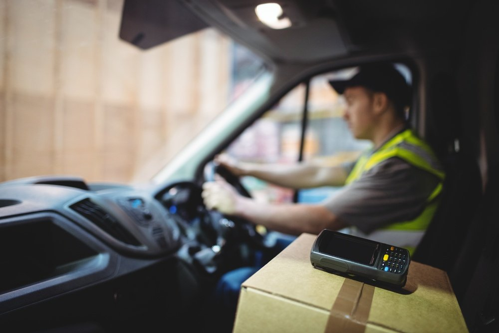 Delivery driver driving van with parcels on seat outside warehouse-1